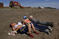 Rabotkina Lyubov left, (31), Malykhina Olesya (35) and Saltaev Oleg (14) sit in the sun outside the fish processing plant during a break from work in the small settlement of Vyvenka at the mouth of the Vyvenka river July 24, 2007.