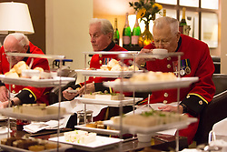 © Licensed to London News Pictures. 31/03/2014. London, UK. Chelsea Pensioners attend a 'Rosa Lewis' afternoon tea at The Cavendish hotel in Mayfair, London. The afternoon tea will be served during April and the hotel will make a donation to the Chelsea Hospital for every tea ordered in support of the 100th anniversary celebrations of the Great War. Photo credit : Vickie Flores/LNP