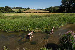 © Licensed to London News Pictures. 07/08/2020. CHORLEYWOOD, UK. Thomas (L), aged 10, and Noah, aged 6, play in the cool waters of the River Chess near Chorleywood, Hertfordshire.  The forecast is for temperatures to continue to exceed 30C for the next few days. (Parental permission obtained)  Photo credit: Stephen Chung/LNP