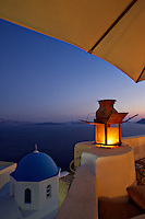 A glowing lantern on the edge of a porch overlooking the Aegean Sea at dusk, Santorini, Greece