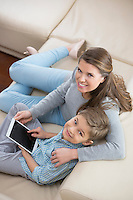 High angle portrait of mother and son with tablet PC sitting on sofa