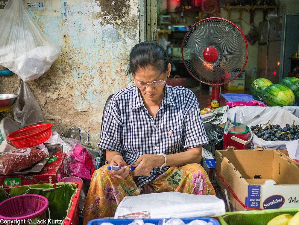 20 APRIL 2013 - BANGKOK, THAILAND:   A woman in her fruit stall in Talat Noi (Talat means Market, Noi means Small. Literally Small Market). The Talat Noi neighborhood in Bangkok started as a blacksmith's quarter. As cars and buses replaced horse and buggy, the blacksmiths became mechanics and now the area is lined with car mechanics' shops. It is one the last neighborhoods in Bangkok that still has some original shophouses and pre World War II architecture. It is also home to a  Teo Chew Chinese emigrant community.   PHOTO BY JACK KURTZ