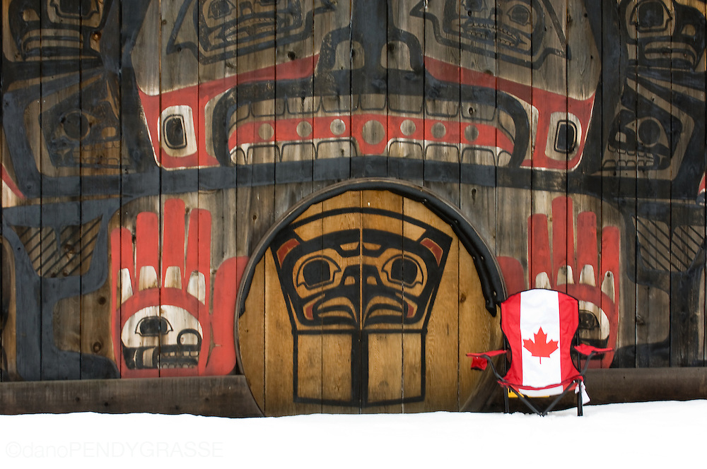 A &quot;Canada Flag&quot; lawn chair sits in front of a highly decorated longhouse in a first nations community outside of <br /> Terrace, BC.