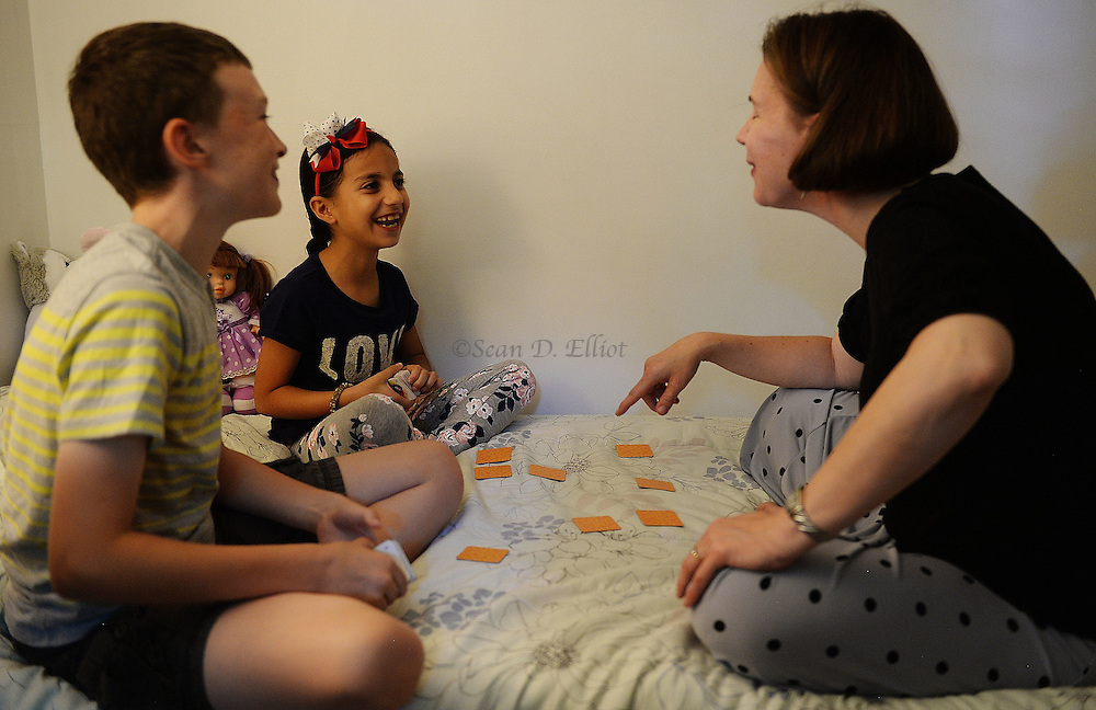 6/30/16 :: REGION :: LYNCH :: Bonnie, right, and Henry Denton work on English language using a matching game with Fulla, 7, Thursday, June 30, 2016. Hasan Mahmoud and Fahima Jemmo and their children Fidan, 17, Hanif, 15 and Fulla, 7, are refugees from the conflict in Syria and lived for three years in Turkey before finally receiving approval to come to the United States. (Sean D. Elliot/The Day)