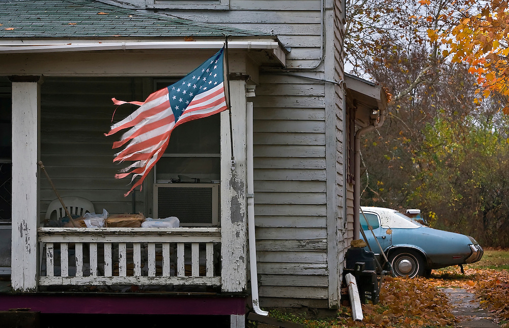 A faded American flag flapped in the breeze on the porch at 615 N. 3rd Street in Lawrence, Kansas amid the fall leaves still hanging on the trees in the November chill.