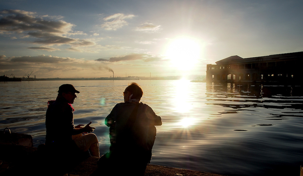 Old friends chat and  watch as the sun rises over Havana Harbour. Travel images from Havana Cuba. Pictures by Chris Pavlich Photography.