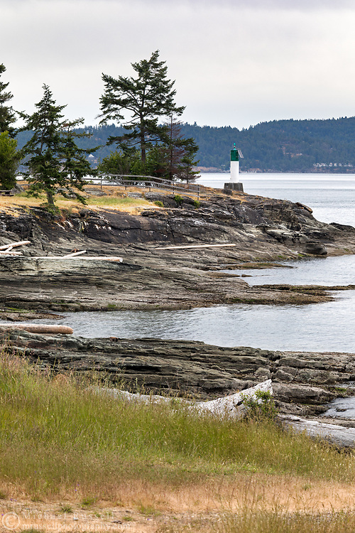 View of the shoreline and Lighthouse at Ruckle Provincial Park on Salt Spring Island, British Columbia, Canada. Photographed from the Ruckle Campground.  North Pender Island and Swanson Channel are in the background.