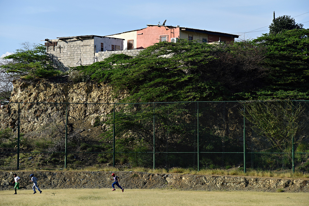 WILLEMSTAD, CURACAO - DECEMBER 11, 2014: Many people attribute the good shortstops that Curacao produces to the crummy fields they learn on, where bad bounces are the norm. Here, the Marchena Hardware 7-9 year old team runs laps around the outfield wall at Parke Shon Ki Nicasia in Willemstad before practice. (photo by Melissa Lyttle)
