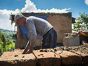 03 AUGUST 2015 - SANKHU, NEPAL: A man repairs a home destroyed by the earthquake in Sankhu, a community about 90 minutes from central Kathmandu. He is using bricks recycled from the original home and mud from the earthquake rubble as mortar.  The Nepal Earthquake on April 25, 2015, (also known as the Gorkha earthquake) killed more than 9,000 people and injured more than 23,000. It had a magnitude of 7.8. The epicenter was east of the district of Lamjung, and its hypocenter was at a depth of approximately 15 km (9.3 mi). It was the worst natural disaster to strike Nepal since the 1934 Nepal–Bihar earthquake. The earthquake triggered an avalanche on Mount Everest, killing at least 19. The earthquake also set off an avalanche in the Langtang valley, where 250 people were reported missing. Hundreds of thousands of people were made homeless with entire villages flattened across many districts of the country. Centuries-old buildings were destroyed at UNESCO World Heritage sites in the Kathmandu Valley, including some at the Kathmandu Durbar Square, the Patan Durbar Squar, the Bhaktapur Durbar Square, the Changu Narayan Temple and the Swayambhunath Stupa. Geophysicists and other experts had warned for decades that Nepal was vulnerable to a deadly earthquake, particularly because of its geology, urbanization, and architecture.    PHOTO BY JACK KURTZ