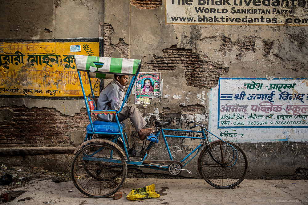 Man sitting in his rickshaw waiting for a client. Vrindavan, India