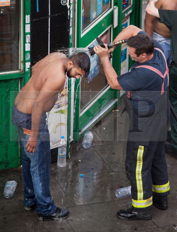 © Licensed to London News Pictures. 25/07/2017. London, UK. A victim of what is thought to have been an acid attack has water poured on his head by a fireman - on the side of the road in Bethnal Green. Two men have been taken to hospital after flagging down police for help. Photo credit: Liam Creighton/LNP