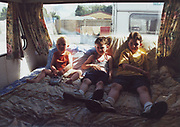 Three kids sitting on a bed in a caravan, Winterbourne Travellers site, Bristol, 1990's
