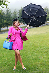 Not so Glorious Goodwood… A race goer get's caught up in the rain and wind as she arrives for  the opening day of Glorious Goodwood in the UK, Tuesday, 30th July 2013 <br /> Picture by Stephen Lock / i-Images