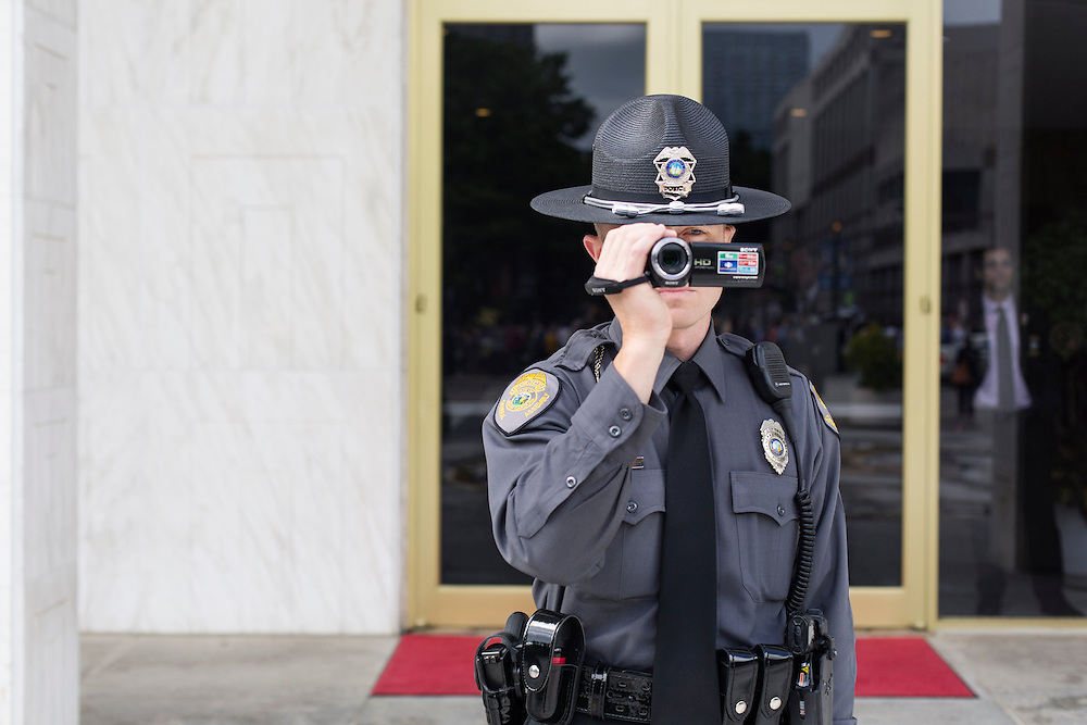 """A General Assembly Police officer records a """"Moral Monday"""" demonstration outside the North Carolina Legislature Building on May 20, 2013. Nearly 300 people have been arrested over five weeks of """"Moral Monday"""" demonstrations in opposition to the recent policies of the Republican leadership . The NAACP contends these arrests may violate First Amendment rights."""