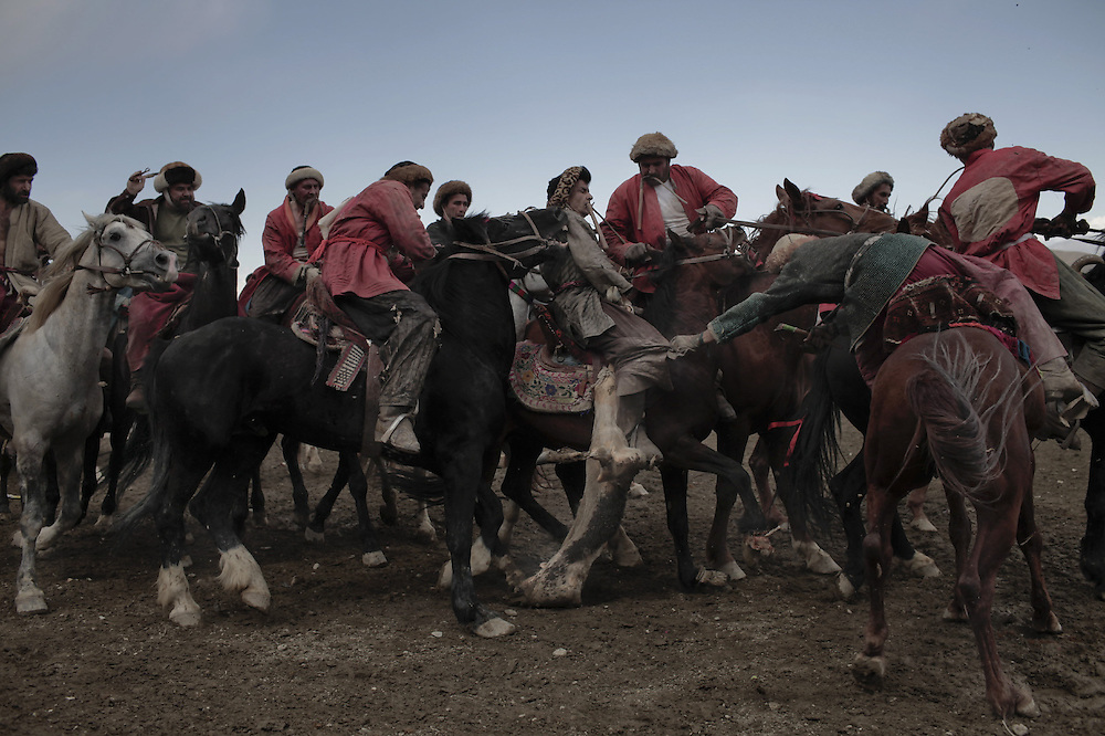Afghan horsemen compete for the goat carcass during a game of buzkashi in Kabul on April 23, 2010. The ancient game is an Afghan national sport, played between two teams of horsemen competing to throw a goat carcass into a scoring circle. AFP PHOTO/Mauricio LIMA