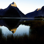 Mitre Peak at sunrise. Mitre Peak is an iconic mountain in the South Island of New Zealand. It is one of the most photographed peaks in the country. Part of the reason for its iconic status is its location. Close to the shore of Milford Sound, in the Fiordland National Park in the southwestern South Island, it is a stunning sight. Rising to 1,692 metres from the water of the sound. it is actually a closely grouped set of five peaks, although from most easily accessible viewpoints it appears as a single point. Milford Sound,  Milford Sound, New Zealand. 30th April 2011. Photo Tim Clayton
