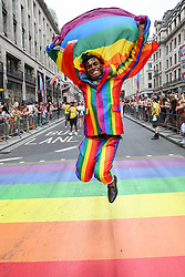 © Licensed to London News Pictures. 06/07/2019. London, UK. A participant dressed in rainbow colours outfit jumps at the rainbow coloured crossing at the annual Pride Parade in central London. An estimated over 1 million people lined along the route in support of the LGBT (Lesbian, Gay, Bisexual and Transgender/Transsexual) community. Photo credit: Dinendra Haria/LNP