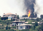 Flames explode next to house in a mountain subdivision in the Waldo Creek fire west of Colorado Springs, Colorado June 24, 2012.  Firefighters in Western U.S. states struggled to contain out-of-control wind-stoked wildfires across the U.S. west as summer temperatures mounted, and a fresh blaze consumed more homes in Colorado.  REUTERS/Rick Wilking (UNITED STATES)