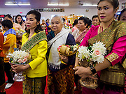 14 APRIL 2019 - DES MOINES, IOWA: Women line up to make an offering in the Tak Bat during Lao New Year, also called Songkran,  observances at Wat Lao Buddhavath in Des Moines. Several thousand Lao people live in Des Moines. Most came to the US after the wars in Southeast Asia. Songkran is celebrated in Theravada Buddhist countries (Sri Lanka, Myanmar, Thailand, Laos, and Cambodia) and in Theravada Buddhist communities around the world.      PHOTO BY JACK KURTZ