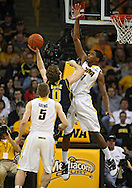 February 19 2011: Michigan Wolverines guard/forward Zack Novak (0) tries to shoot over Iowa Hawkeyes forward Melsahn Basabe (1) as Iowa Hawkeyes guard Matt Gatens (5) looks on during the first half of an NCAA college basketball game at Carver-Hawkeye Arena in Iowa City, Iowa on February 19, 2011. Michigan defeated Iowa 75-72 in overtime.