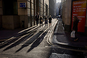 A tall man looks down at shorter women as they walk through winter sunlight down Abchurch Lane, EC4, in the City of London.