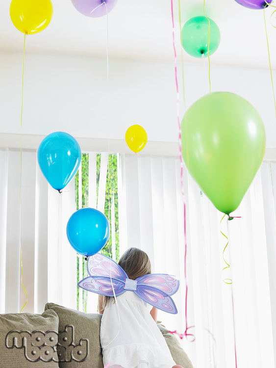 Young girl (7-9) climbing on sofa wearing fairy wings back view