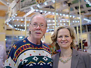 """Garden City, New York, USA. March 9, 2019. R-L, Nassau County Executive LAURA CURRAN and BOB STUHMER pose in front of Nunley's Carousel during Unveiling Ceremony of mural by painter Michael White. Stuhmer arranged all the organ music for the carousel, including the instrumental piece Billy Joel wrote """"Waltz #1 (Nunley's Carousel)"""" in 2001.  Event was held at historic Nunley's Carousel in its Pavilion on Museum Row on Long Island."""