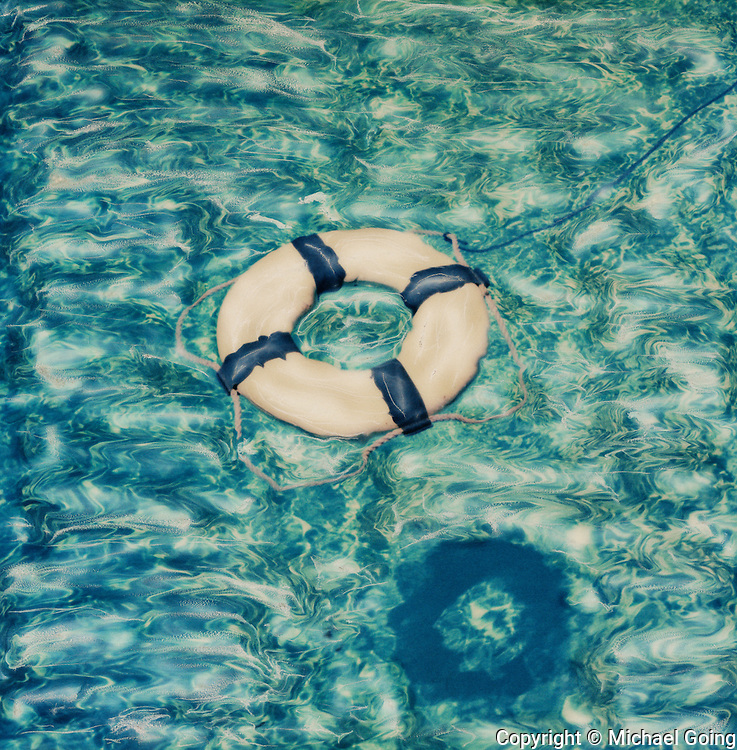 Life ring with rope line and cast shadow floating in pool