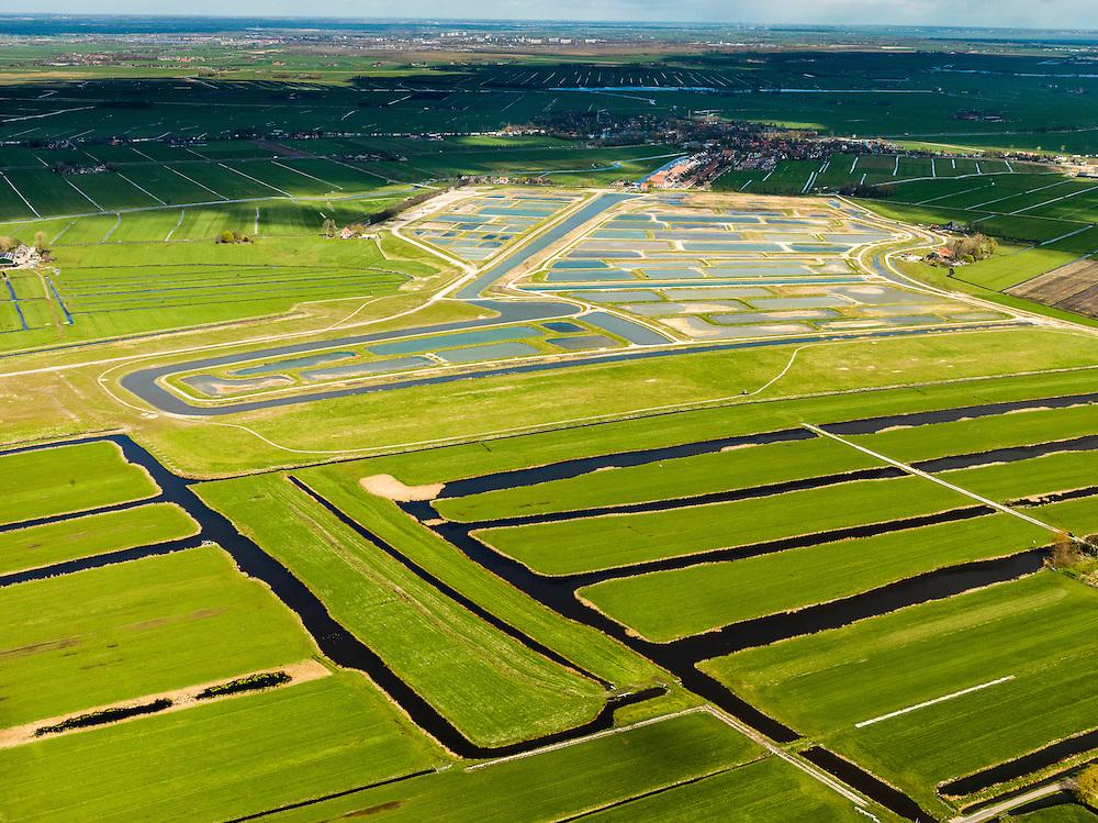 Nederland, Noord-Holland, Amsterdam (landelijk Noord), 16-04-2012; Waterland. Veenderij Zunderdorp en op het tweede plan de Volgermeerpolder. De polder maakte oorspronkelijk ook deel uit van de veenderij, tot in de jaren '50 is hier turf gewonnen. Na beeindiging van het vervenen werden de 'petgaten' volgestort met huisvuil en chemisch afval, onder andere met dioxine en benzeen afkomstig van Philips-Duphar..Inmiddels is de polder gesaneerd, de voormalige vuilstortplaats is afgedekt met folie en voorzien van en afdeklagen, bestaande uit zowel grond als ook water. Het ontwerp voorziet in een natuurgebied met 'sawa's' waarin nieuw veen zich kan ontwikkelen wat de vervuilde grond verder zal isoleren (natural capping). .The Volgermeerpolder in the rural area near Amsterdam once a landfill site for heavily polluted household and industrial waste, has been cleaned up using natural capping and turned into a nature area. .luchtfoto (toeslag), aerial photo (additional fee required);.copyright foto/photo Siebe Swart