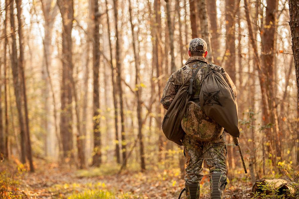 Lone hunter walking through woods.Turkey hunter walking through the woods calling