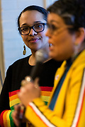 Ali Muldrow looks on as Ananda Mirilli speaks to the crowd at the Madison School Board election watch party at Robinia Courtyard in Madison, Wisconsin, Tuesday, Feb. 19, 2019.