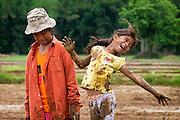 Thai children play in the mud during planting season in Nakhon Nayok, Thailand