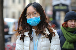 © Licensed to London News Pictures. 14/02/2020. London, UK. A fashion enthusiast wearing a surgical face mask arrives for the London Fashion Week shows in The Strand. The latest Coronavirus patient in London is linked to 'super spreader' attended transport conference with 250 people in Westminster. Photo credit: Dinendra Haria/LNP