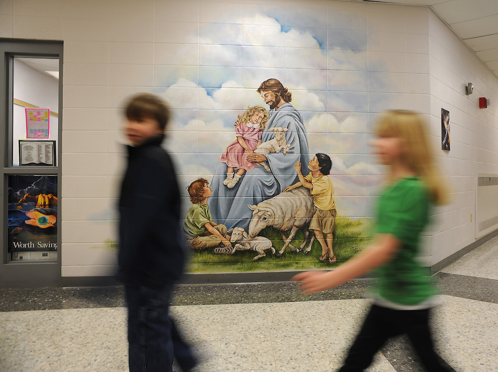 Religious education students from St. John the Baptist Parish in Howard, Wis., walk past a mural of Jesus the Good Shepherd on Jan. 27. (Sam Lucero photo)