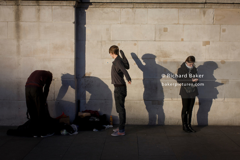 Young people whose shadows are on the wall of the National Portrait Gallery in Trafalgar Sq, London.