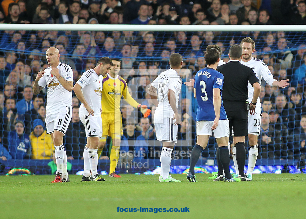 Jonjo Shelvey (left) of Swansea City leaves the field after being sent off by referee Kevin Friend during the Barclays Premier League match against Everton, at Goodison Park, Liverpool.<br /> Picture by Michael Sedgwick/Focus Images Ltd +44 7900 363072<br /> 01/11/2014