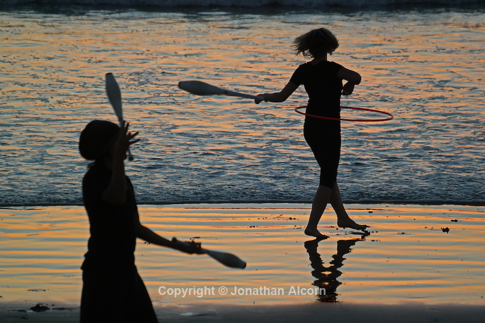 A juggler and a girl practicing hooping, artistic movement and dancing with a hoop, on Venice Beach at sunset on a warm January day in Southern California.