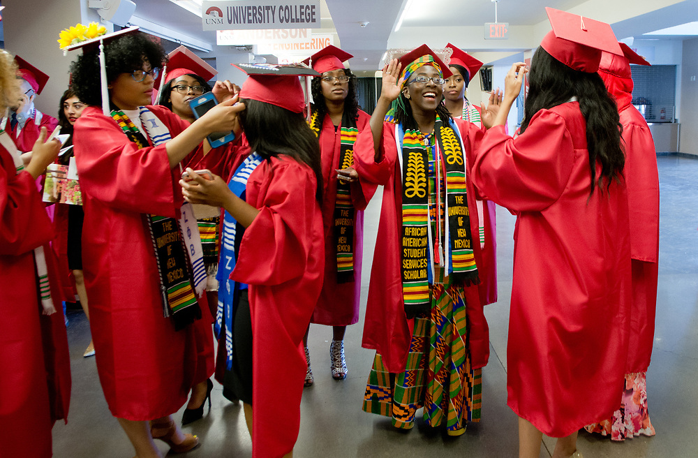 mkb051317a/metro/Marla Brose --  University of New Mexico graduates, including Jacklyn Asamoah, second from right, gather on the concourse to chat, take selfies and make final cap and gown adjustments before UNM's commencement ceremony, Saturday, May 13, 2017, in Albuquerque, N.M. Asamoah is earning a B.S. in Medical Lab Sciences. (Marla Brose/Albuquerque Journal)