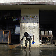 A young boy sweeps mud and water out of a flooded store in the fishing village of Perumalpettai in Tamil Nadu, India on January 17, 2005, after the area was struck by the Indian Ocean Tsunami on December 26, 2004, killing 37 of the villagers and destroying nearly all of their fishing boats. Generated by an earthquake on the ocean floor, the tsunami devastated the fishing industry along the southeastern coast of India.