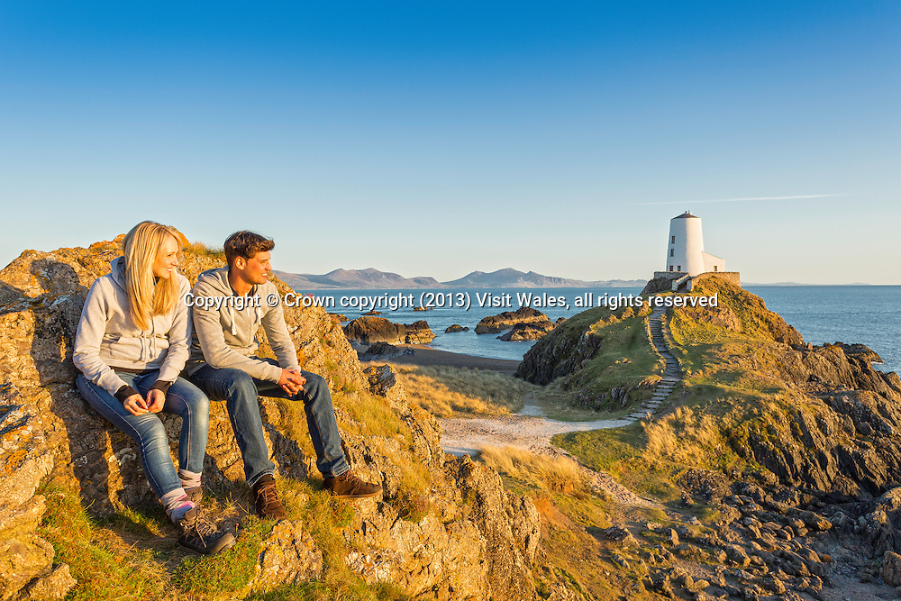 Couple looking out past lighthouse at sunset<br /> Llanddwyn Island<br /> Near Newborough<br /> Anglesey<br /> North<br /> Walking<br /> Activities and Sports