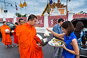 "21 JULY 2013 - BANGKOK, THAILAND:  A woman gives food to a monk and makes merit at Wat Benchamabophit on the first day of Vassa, the three-month annual retreat observed by Theravada monks and nuns. On the first day of Vassa (or Buddhist Lent) many Buddhists visit their temples to ""make merit."" During Vassa, monks and nuns remain inside monasteries and temple grounds, devoting their time to intensive meditation and study. Laypeople support the monastic sangha by bringing food, candles and other offerings to temples. Laypeople also often observe Vassa by giving up something, such as smoking or eating meat. For this reason, westerners sometimes call Vassa the ""Buddhist Lent.""       PHOTO BY JACK KURTZ"