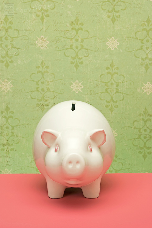 A white ceramic piggy bank on a pink surface and a green patterned design wallpaper backgrouund.