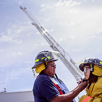 040415       Cable Hoover<br /> <br /> McKinley West firefighter Ervin Yazzie straps Summer Martinez into firefighter gear during the Spring Fling at For Canyon Park in Gallup Saturday.