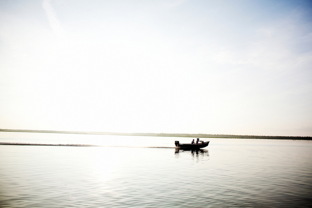 "A boat of ""weekend warriors"" glides over the water next to the boat manned by Julius and Rebel as they leave early in the morning for alligator hunting near Shell Island, Louisiana on Saturday, September 19, 2009. ""Weekend warriors"" is a derogatory term the locals apply to individuals who come to the river for recreation."