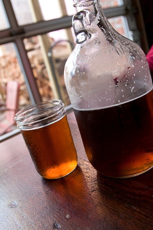 Brooklyn, NY: A half gallon glass jug of beer, otherwise known as a growler sitting on a table at a barbecue restaurant.