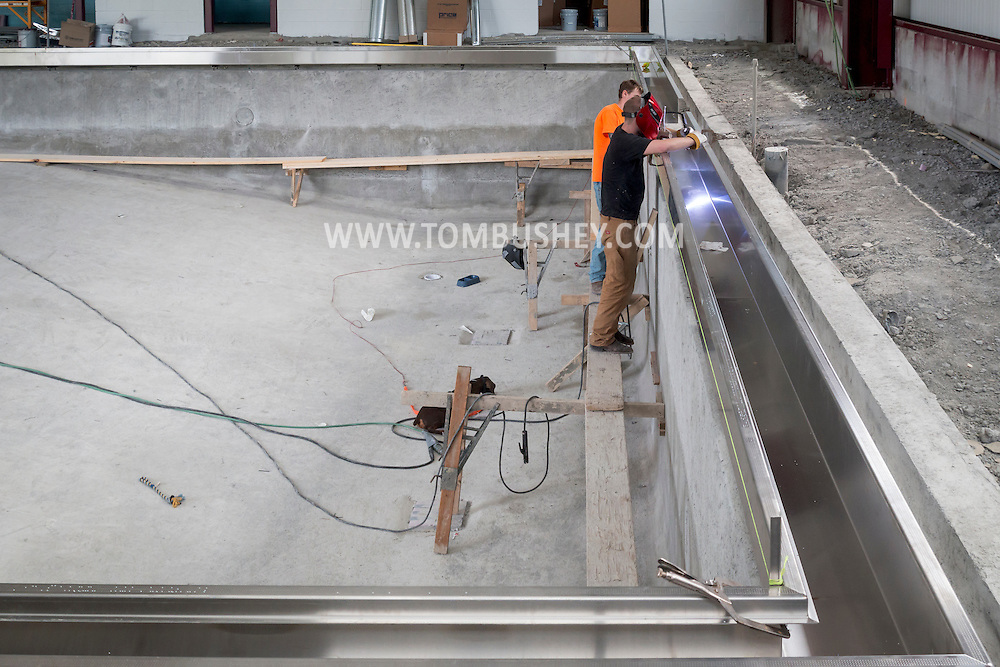 Middletown, New York - Workers from Royals Pools and Spas install splash gutters at the pool under construction at the YMCA of Middletown on July 13, 2016.