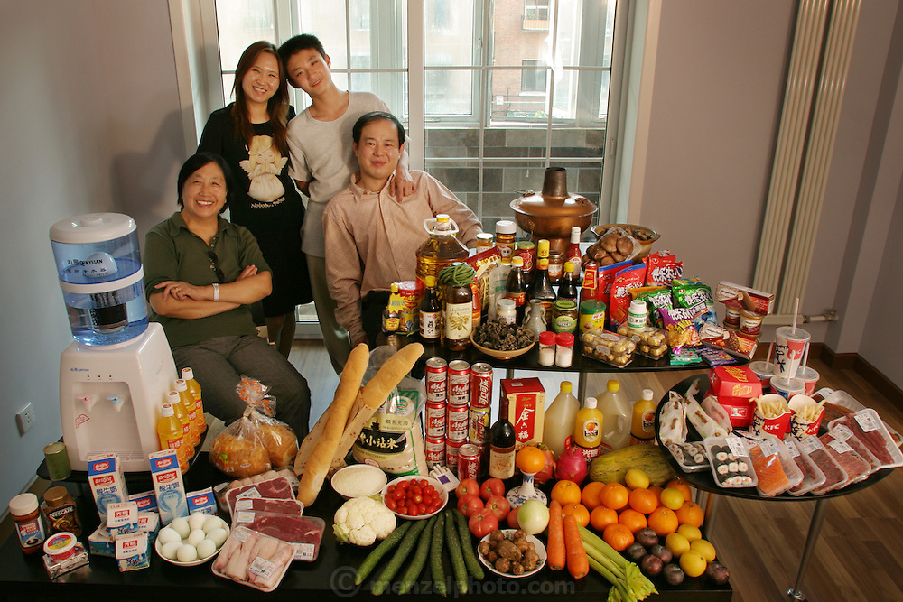 (MODEL RELEASED IMAGE). The Dong family in the living room of their one-bedroom apartment in Beijing, China, with a week's worth of food. The Dong family is one of the thirty families featured in the book Hungry Planet: What the World Eats (p. 74).