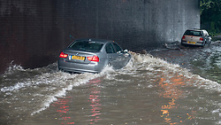 © Licensed to London News Pictures. 23/06/2016. London, UK. As rainwater collects under the railway bridge on the Rickmansworth Road, some drivers resort to driving on the submerged pavement to try to pass through as a torrential rain shower lasting for more than 30 minutes causes localised flooding in Northwood, north west London. Photo credit : Stephen Chung/LNP