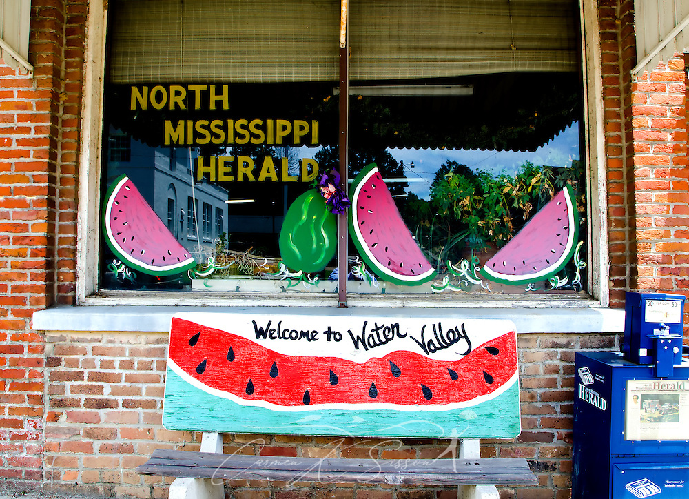 Painted watermelons decorate the window and bench outside the North Mississippi Herald newspaper office in Water Valley, Mississippi. (Photo by Carmen K. Sisson/Cloudybright)