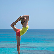 Young women standing on beach wall doing yoga
